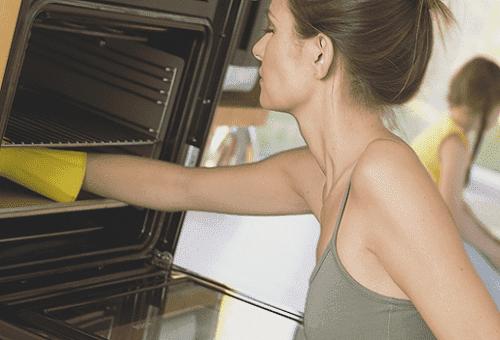женщина чистит духовку