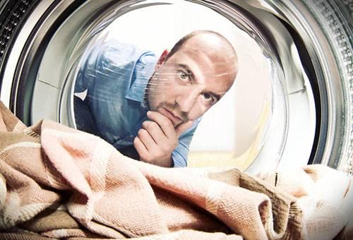 Мужчина наблюдает за стиркой в стиральной машине