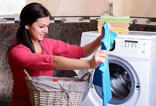 Женщина достает белье из стиральной машины