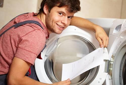 Мужчина изучает инструкцию к стиральной машине