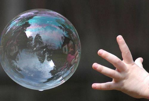рука ребенка у мыльного пузыря