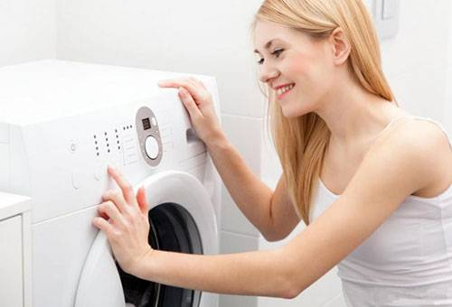 Девушка отключает стиральную машину