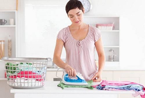 Женщина гладит детские вещи