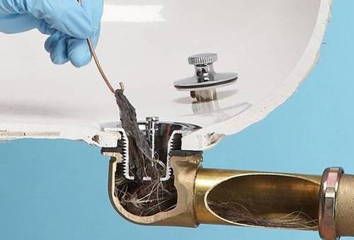 Извлечение предметов из слива раковины проволокой