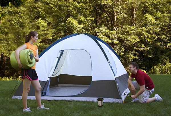 Молодые люди на природе ставят палатку