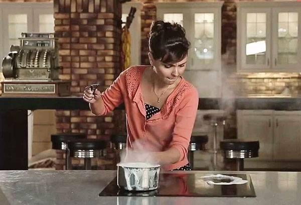 Девушка готовит на стеклокерамической плите