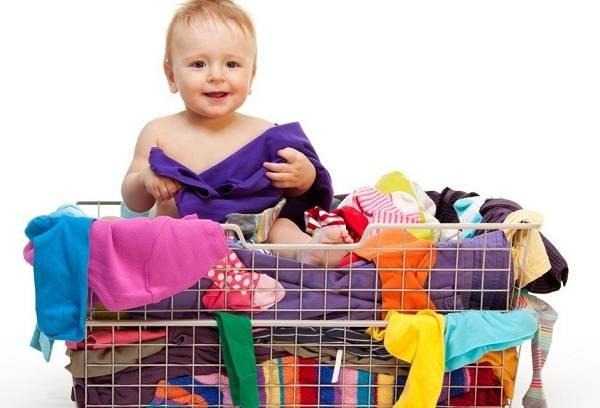 ребенок и детская одежда в корзине