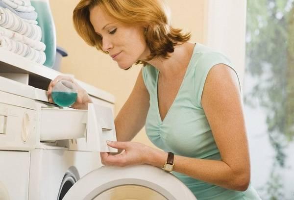 женщина заливает гель в стиральную машину