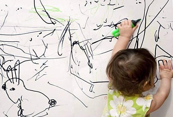 Ребенок рисует на белой стене