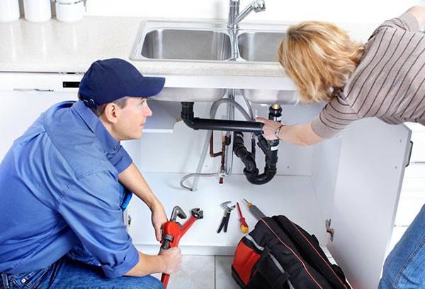 Женщина показывает сантехнику течь под раковиной