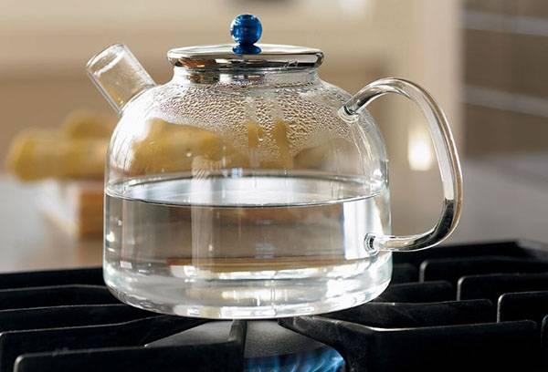 Стеклянный чайник на плите