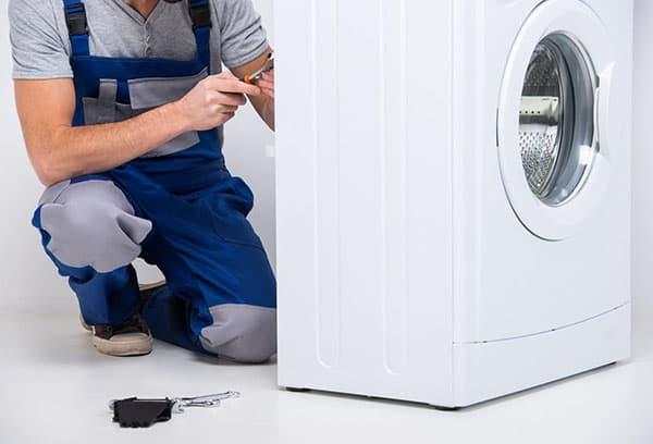 Мастер разбирает стиральную машину