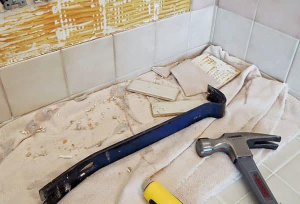Процесс демонтажа старой плитки в ванной