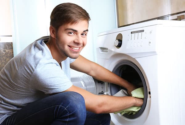 Мужчина достает белье из стиральной машины