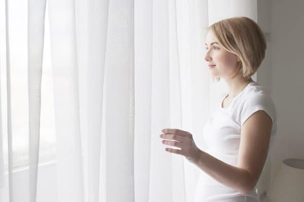 Девушка у окна с белой гардиной
