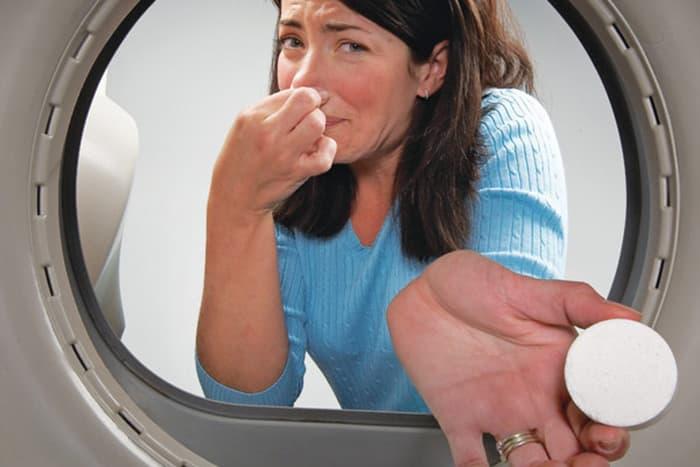 Женщина добавляет таблетку в барабан стиральной машины