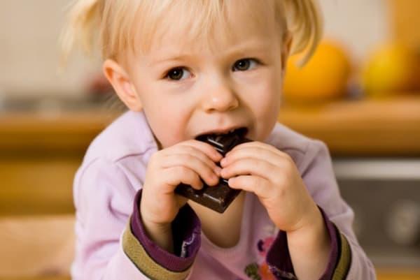 Маленькая девочка ест гематоген