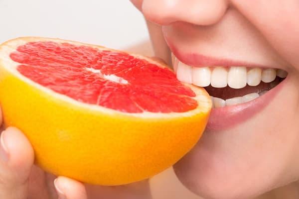 Женщина ест грейпфрут