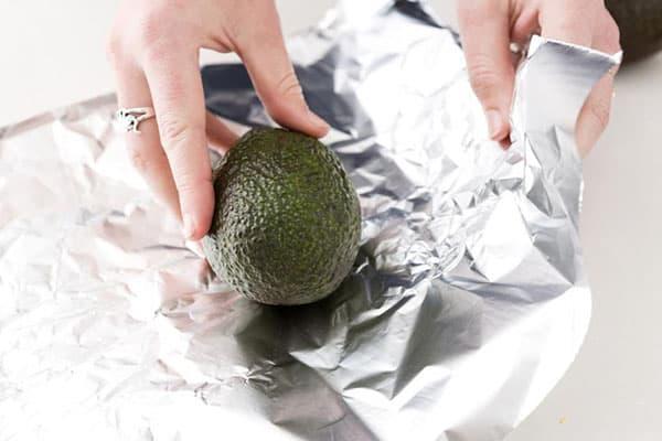 Женщина заворачивает авокадо в фольгу