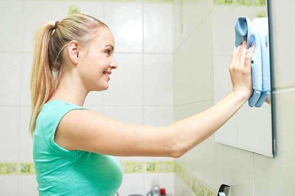 Девушка протирает зеркало в ванной