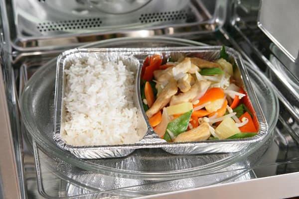 Еда в контейнере из фольги в микроволновке