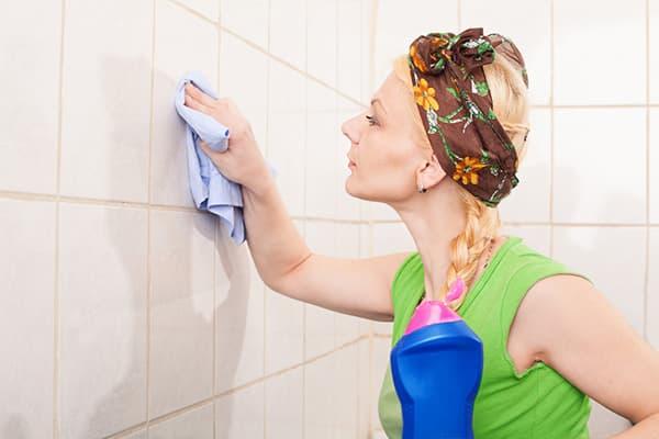 Девушка моет плитку на стене в ванной