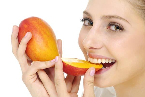 Девушка ест манго