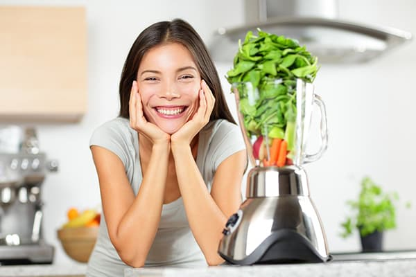 Девушка делает смузи из шпината