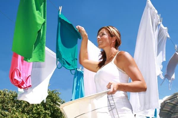 Девушка развешивает чистое белье