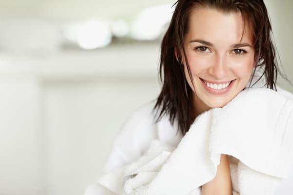 Девушка вытирается большим полотенцем