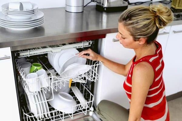 Девушка достает тарелки из посудомоечной машины