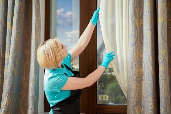 Девушка проверяет чистоту штор