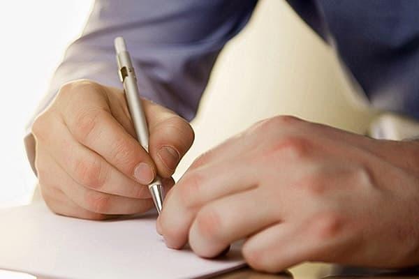 Мужчина пишет в блокноте