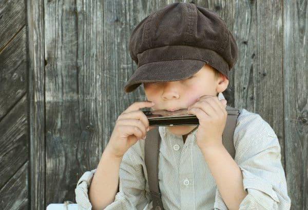 Мальчик играющий на губной гармошке