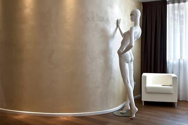 Скульптура у стены с декоративной штукатуркой