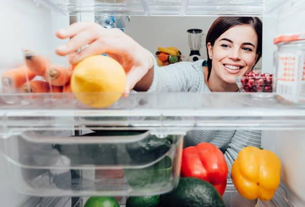 Девушка кладет лимон в холодильник