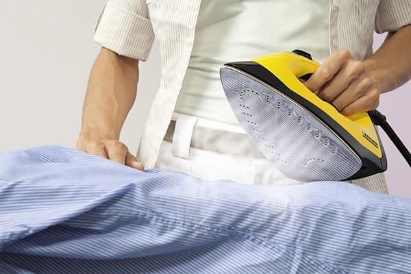 Мужчина гладит сорочку паровым утюгом