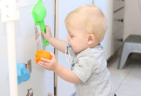 Играющий ребенок у холодильника