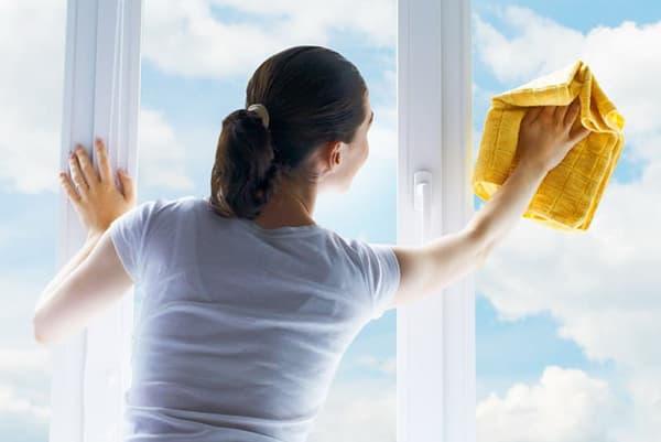 Женщина моет окно в солнечную погоду
