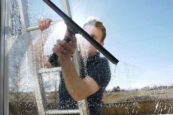 Мужчина моет окно