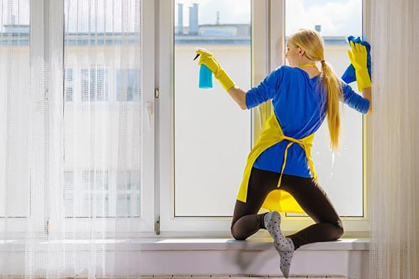Девушка на подоконнике моет окно