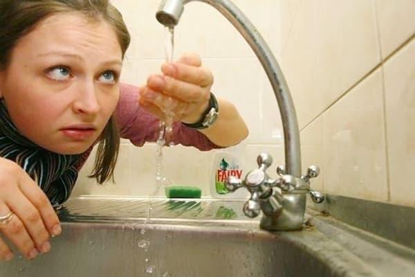 Женщина рассматривает воду из-под крану