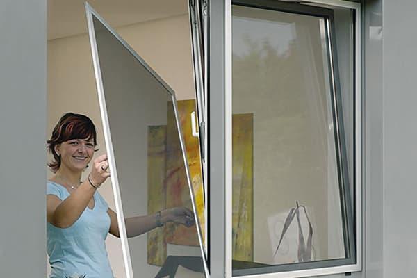 Женщина снимает сетку с окна