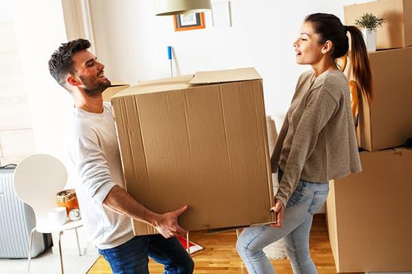Мужчина и женщина несут большую коробку