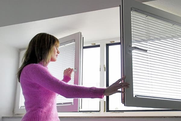 Девушка открывает окно для проветривания