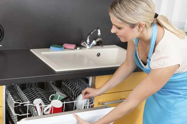 Женщина загружает посуду в посудомоечную машину