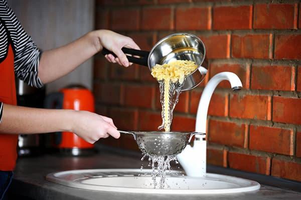 Женщина сливает воду после варки макарон
