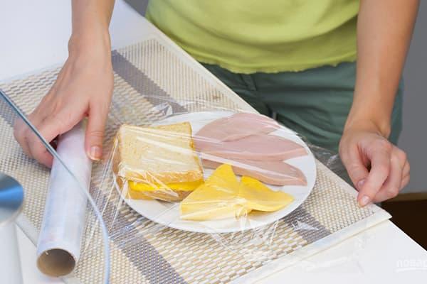 Упаковка тарелки с завтраком пищевой пленкой