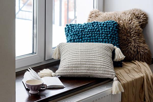 Подушки, чашка и книга на подоконнике