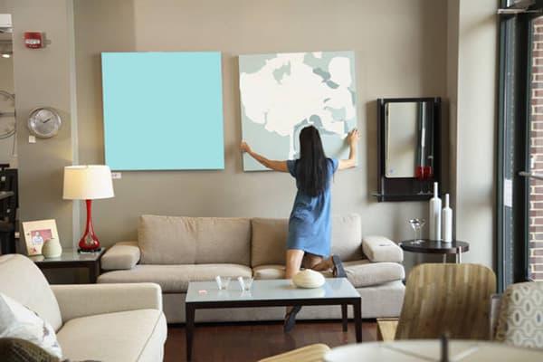 Девушка снимает картину со стены